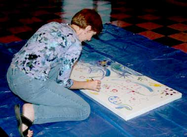 Jan Dodgins participating in a group painting project